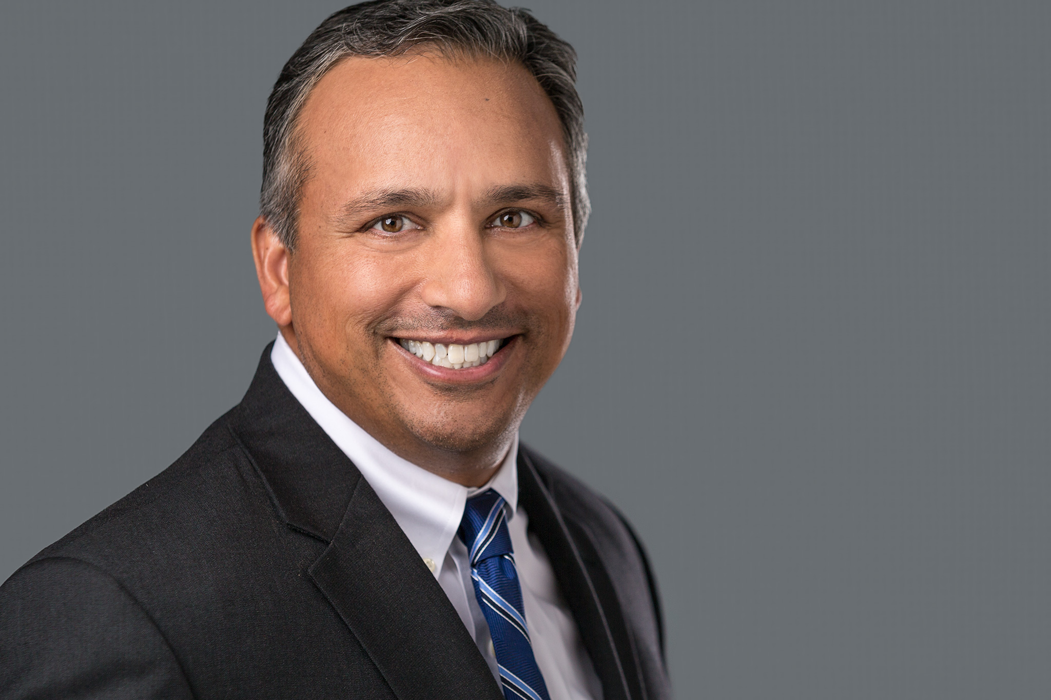 Professional headshot of a middle-aged Indian man smiling.