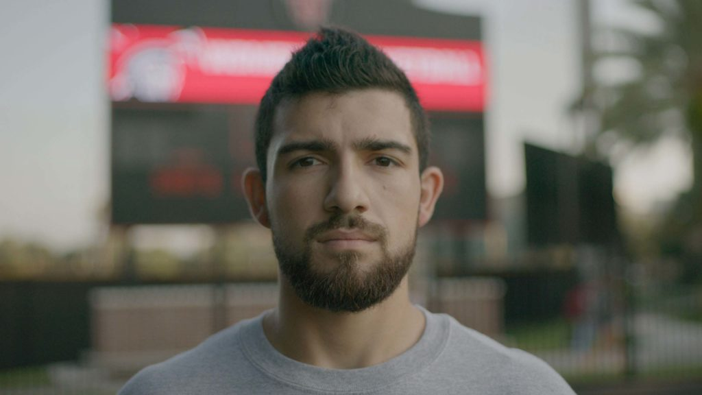 man with beard outside baseball stadium