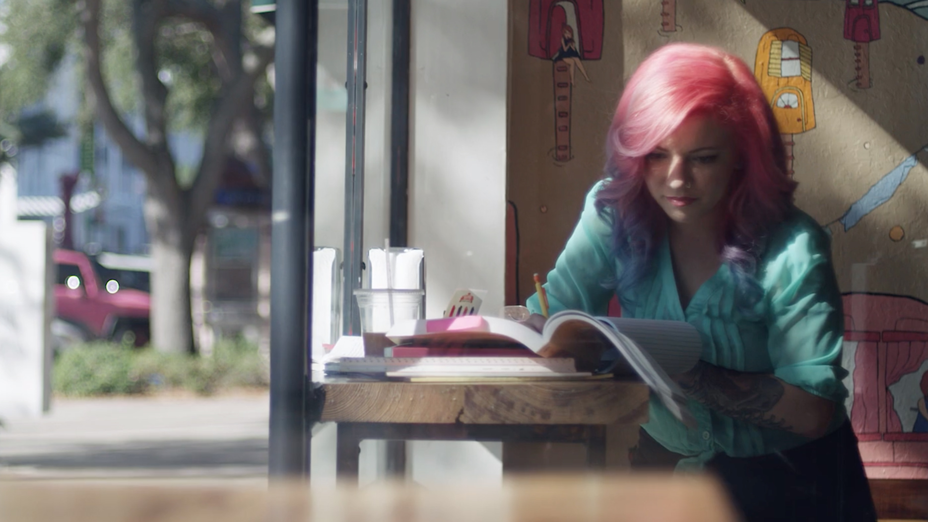 woman with pink hair writing at a bar