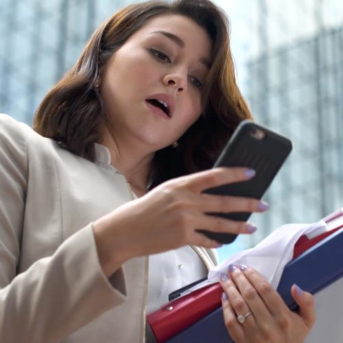 woman looking at her cell phone while carrying binders