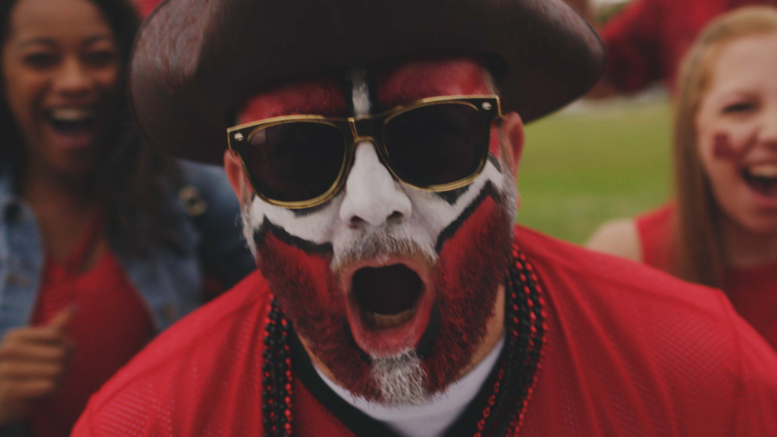 bucs fan with face painted yelling into camera