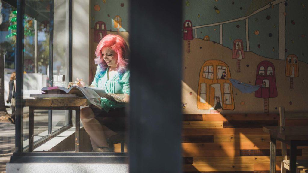 girl with pink hair writing at bar