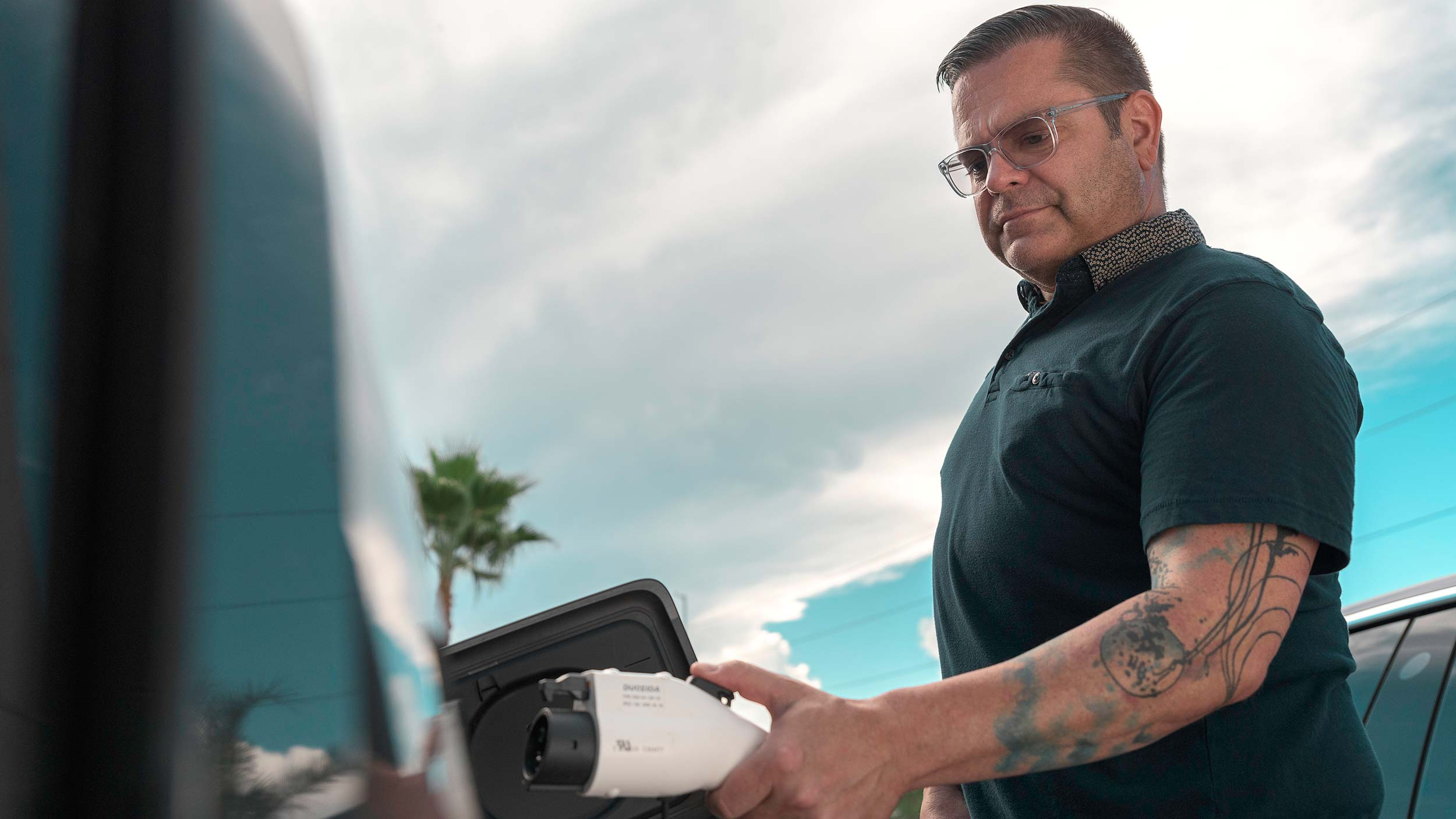 man with tattoos plugging electric car into charger